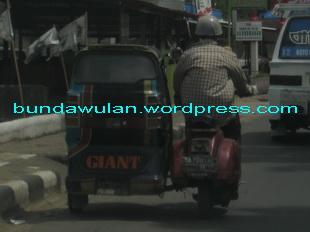 Supir ojek vespa duduk bersila sambil mengendarai vespanya